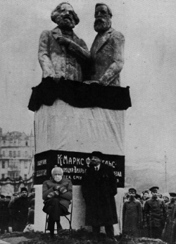 Lenin below Marx-Engels Statue w/ Bernie In Mittens beside him